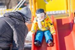 Père extérieur plaçant votre enfant sur la glissière L'enfant est dans le defo Photographie stock libre de droits