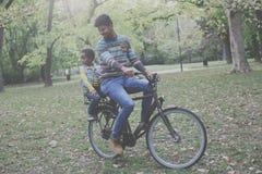 Père gai d'Afro-américain conduisant sa petite fille sur le vélo Photo stock