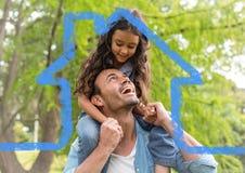 Père gai donnant sur le dos le tour à sa fille contre le contour de maison photos libres de droits