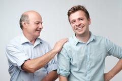 Père gai et fils regardant l'un l'autre souriant photos libres de droits