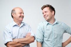 Père gai et fils regardant l'un l'autre souriant photo stock