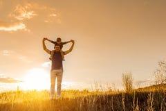 Père gai tenant le garçon près de la vue de coucher du soleil Images libres de droits