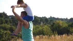 Père gai tenant son fils de sourire sur des épaules et tournant autour au pré le jour ensoleillé d'été Papa et son rouge banque de vidéos