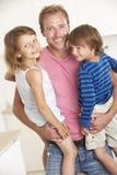 Père Giving Children Cuddle à la maison Photo stock