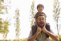 Père Giving Son Ride sur des épaules pendant la promenade Photographie stock libre de droits