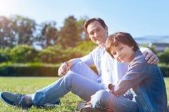 Père harmonieux et fils détendant sur l'herbe ensemble Image stock