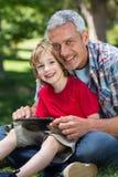 Père heureux à l'aide du PC de comprimé avec son fils photo libre de droits