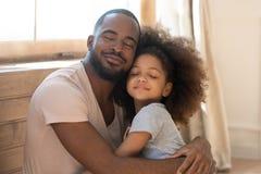 Père heureux aimant de famille d'enfant d'étreinte drôle mignonne africaine de fille photos stock