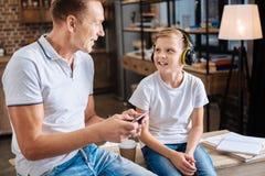 Père heureux allumant la musique pour son fils dans des écouteurs Photo stock