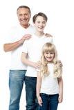 Père heureux avec des enfants se tenant dans la rangée Photographie stock libre de droits