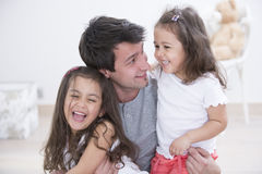 Père heureux avec des filles passant le temps de qualité ensemble à la maison Images stock