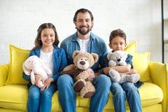 père heureux avec deux enfants adorables tenant des jouets et souriant à la caméra photo libre de droits