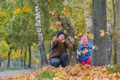 Père heureux avec la petite fille jetant en l'air vers le haut des feuilles d'automne jaunes en parc dehors photo stock