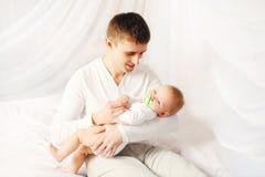 Père heureux avec le bébé sur l'heure du coucher de maison de lit Photos libres de droits