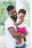 Père heureux avec le bébé sur le divan Images stock