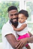 Père heureux avec le bébé sur le divan Photographie stock libre de droits