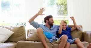 Père heureux avec le fils appréciant devant la télévision clips vidéos