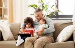 Père heureux avec le fils de préadolescent et de bébé à la maison photographie stock