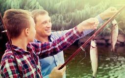 Père heureux avec le fils regardant des poissons sur le crochet photographie stock libre de droits