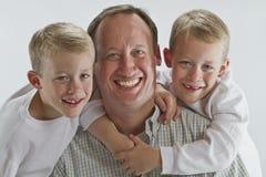 Père heureux avec les jumeaux identiques de 6 années Image stock
