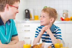 Père heureux avec son fils parlant pendant le petit déjeuner Images libres de droits