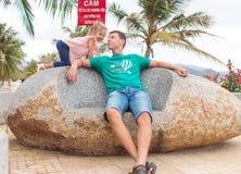 Père heureux avec un enfant s'asseyant sur la pierre près de la plage, ils jouent et sourient photos libres de droits