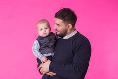 Père heureux avec un fils de bébé d'isolement sur un fond rose Photos libres de droits