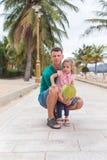 Père heureux avec une étreinte et un sourire d'enfant, ils tiennent une noix de coco photo libre de droits