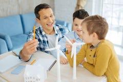 Père heureux causant gaiement avec des fils au sujet du sien le travail Image libre de droits