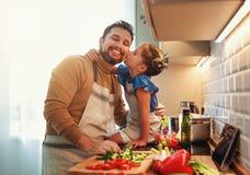 Père heureux de famille avec la fille d'enfant préparant la salade végétale photo stock