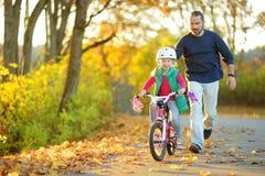 Père heureux enseignant sa petite fille à monter une bicyclette Enfant apprenant à monter un vélo photographie stock libre de droits