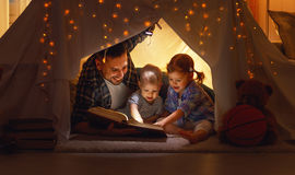 Père heureux et enfants de famille lisant un livre dans la tente au hom Images stock