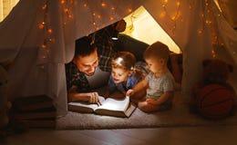 Père heureux et enfants de famille lisant un livre dans la tente au hom Photo stock