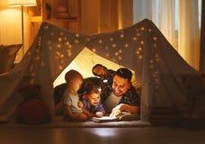Père heureux et enfants de famille lisant un livre dans la tente au hom Photos stock