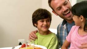 Père heureux et enfants prenant le déjeuner banque de vidéos
