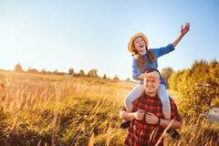 Père heureux et fille marchant sur le pré d'été, ayant l'amusement et le jeu photos stock
