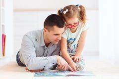 Père heureux et fille passant le temps ensemble en lisant le livre intéressant photos libres de droits