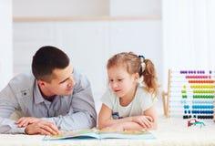 Père heureux et fille passant le temps ensemble en lisant le livre intéressant images stock