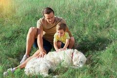 Père heureux et fils ayant des heures de récréation avec leur animal familier Photographie stock libre de droits