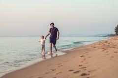 Père heureux et fils ayant le temps de famille de qualité sur la plage dessus image libre de droits