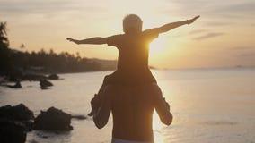 Père heureux et fils dans des lunettes jouant sur le garçon tropical de plage se levant vers le haut des mains imitant un vol au  banque de vidéos