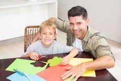 Père heureux et fils faisant les formes de papier ensemble à la table Image libre de droits