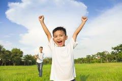 Père heureux et fils jouant dans le pré Image libre de droits