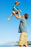 Père heureux et fils jouant sur la plage tropicale, f heureux insouciant Photos libres de droits