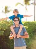 Père heureux et fils jouant sur la plage tropicale, f heureux insouciant Images stock