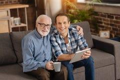 Père heureux et fils pluss âgé posant sur le sofa Image libre de droits