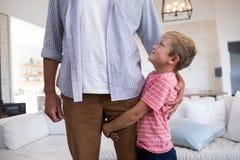 Père heureux et fils s'embrassant dans le salon Photos libres de droits