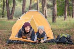 père heureux et fils se situant dans la tente et le sourire photo stock