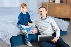 Père heureux et fils souriant tout en dessinant et à l'aide de l'ordinateur portable photographie stock