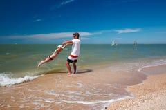 Père heureux et sa fille à la plage ayant l'amusement photographie stock